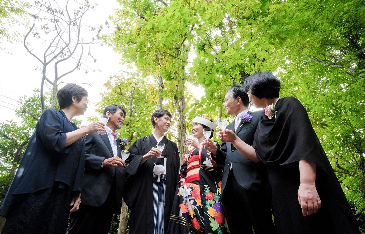 正装したカップルとそれを囲む親族や友人による森の中での結婚式
