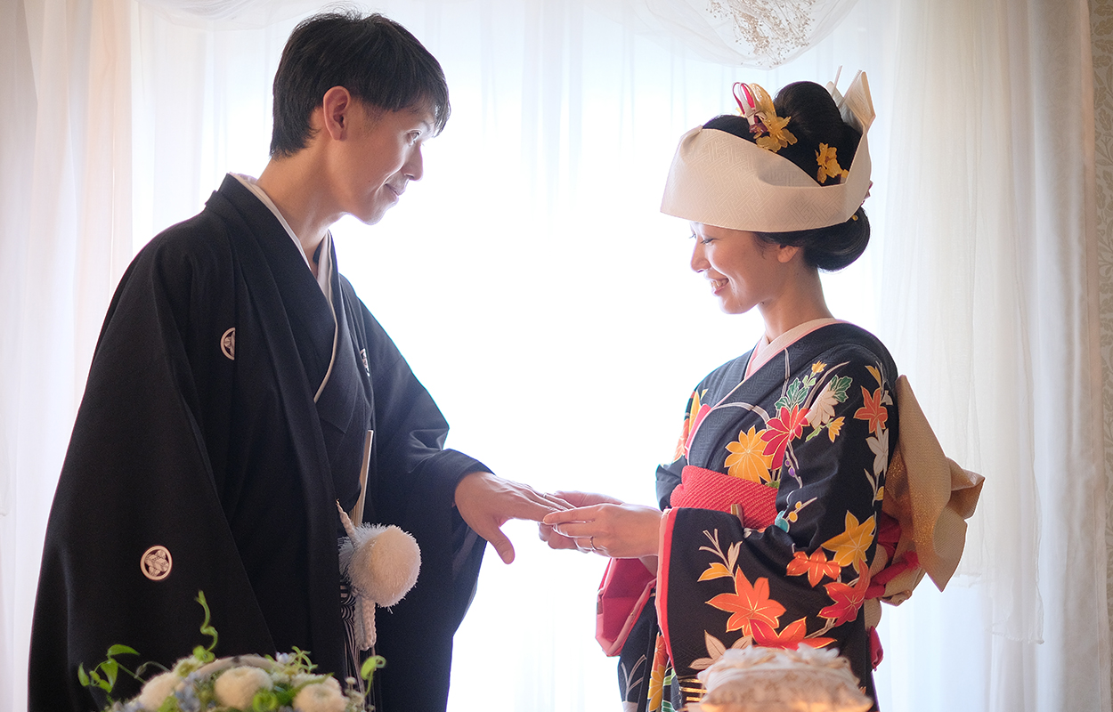 着物姿の女性が、和装の男性に指輪をはめてあげている画像