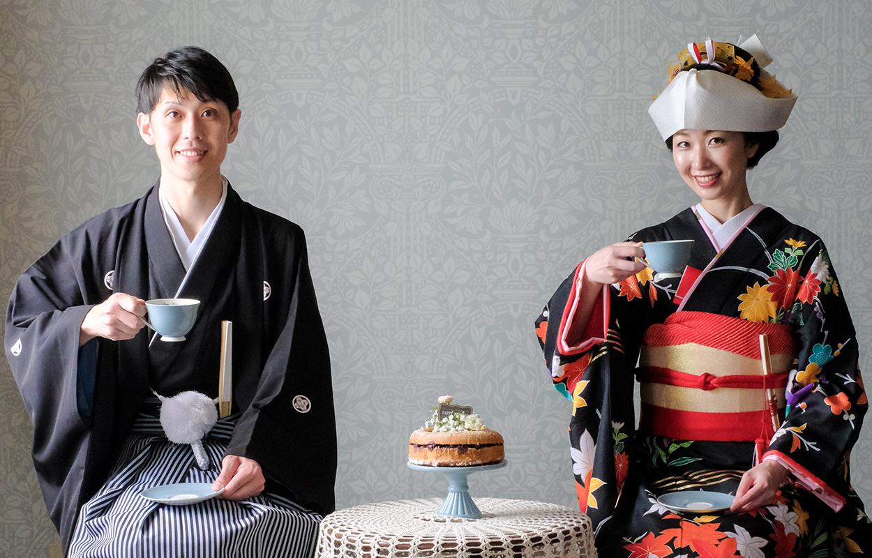 ウェディングフォトのため、和装の男性と着物の女性が笑顔でティーカップを持っている画像