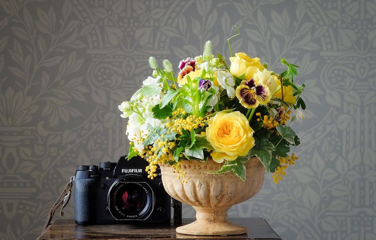 花瓶に生けられた色とりどりの花束と一眼レフカメラの画像